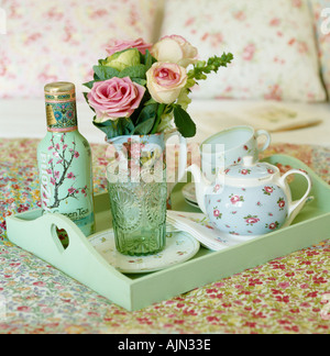 Tea tray on bed with flowers and floral bedspread - Stock Photo