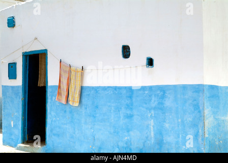 Two towels hanging on a line outside a blue and whitewashed house in the Medina in Asilah - Stock Photo
