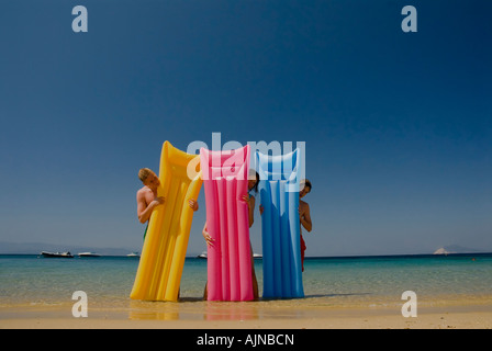 Three people looking out from behind colourful lilos inflatable airbeds sandy beach blue sea and sky Mediterranean - Stock Photo