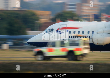British Airways commercial jet passing behind ground crew Land Rover during take off London City Airport, England, - Stock Photo