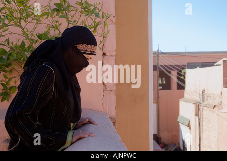 Young Veiled Moslem Woman Peers over the Rooftops of Marrakeesh, Morocco - Stock Photo