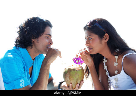 Portrait of a couple sipping on a Coconut drink - Stock Photo