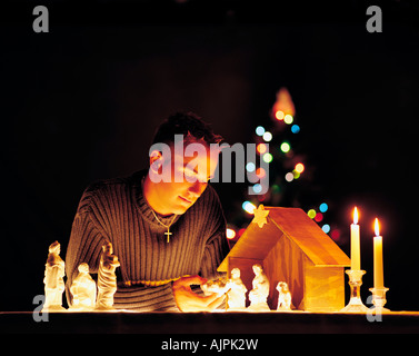 Man with nativity scene figurines and lights - Stock Photo