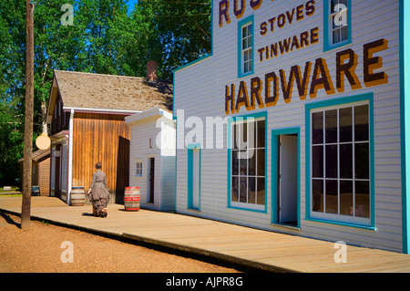 Woman in period dress walking past historic hardware store at Fort Edmonton Park - Stock Photo