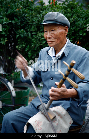 Musician playing an instrument called erhu at the Houhai lake area Beijing China - Stock Photo