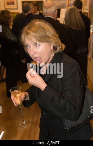 Black tie formal charity dinner London Finger food champagne reception with canapés Cocktail sausage on a stick - Stock Photo