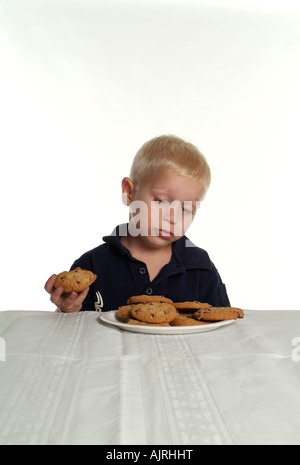 A Two-Year-Old Blond Boy at a table Holding a Chocolate Chip and looking longingly at  a plate of more cookies in - Stock Photo