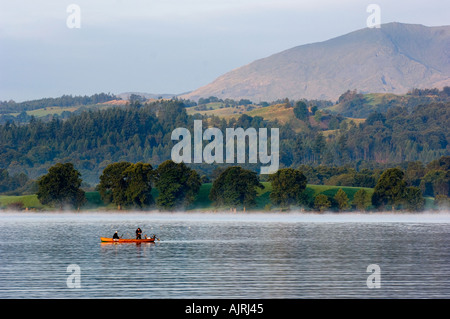 Lake District fishing on Lake Windermere with early morning mist - Stock Photo