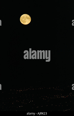 Full moon rising over city lights Belfast Northern Ireland - Stock Photo