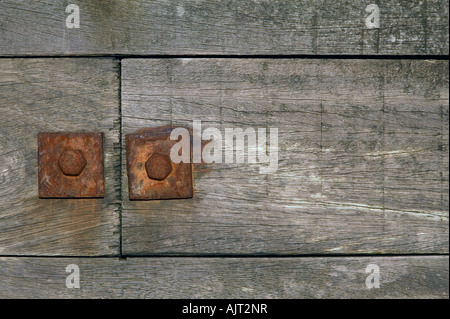 Close up of two rusted nuts on a beach groyne - Stock Photo