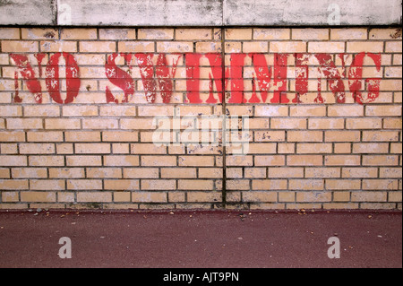 No Swimming stencilled on a brick wall - Stock Photo