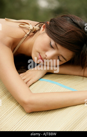 Close-up of a young woman lying on a mat - Stock Photo
