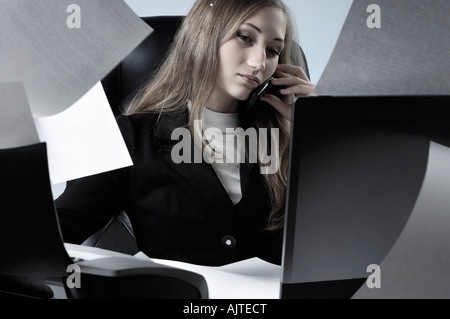 Young businesswoman working in office with paper flying all over the place talking on a cell phone - Stock Photo
