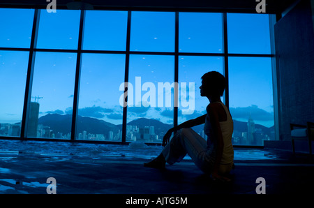 Silhouette of a woman sitting near a hot tub - Stock Photo