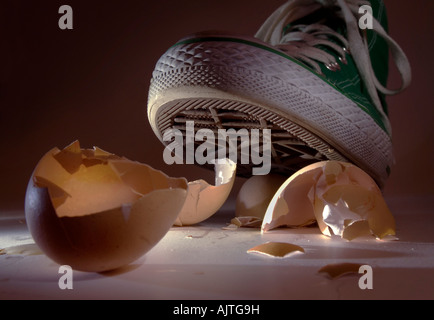 Green sneaker shoe treading on eggshells in close up - Stock Photo