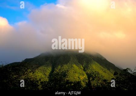 Mount Nevis peak, green volcano peak, Caribbean, leeward islands, cloud cover at the top, blue sky background, national - Stock Photo