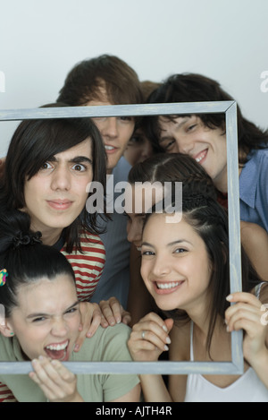 Group of young friends posing for photo, holding up picture frame, smiling at camera, portrait - Stock Photo
