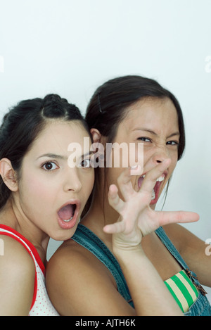 Two young female friends, one snarling at camera, the other with mouth open, portrait - Stock Photo