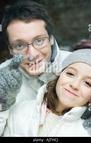 Young man looking over little sister's shoulder and pointing, both smiling at camera, portrait - Stock Photo
