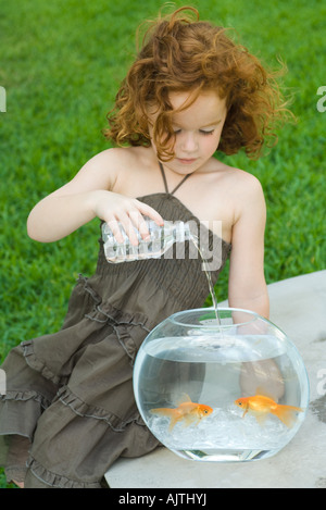 Redheaded little girl pouring bottled water into goldfish bowl - Stock Photo