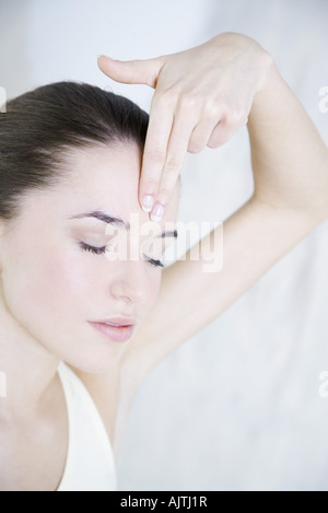Young woman touching forehead, eyes closed - Stock Photo