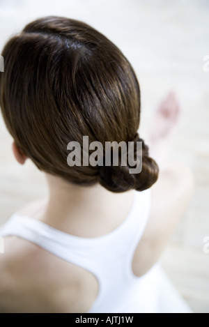 Brunette woman wearing hair in chignon, rear view - Stock Photo