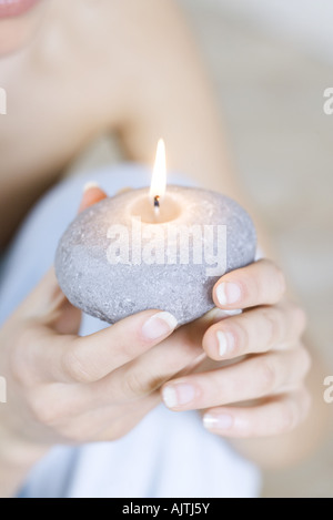 Woman holding burning candle, close-up view of hands - Stock Photo