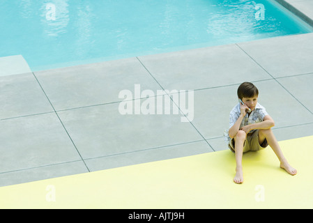Boy sitting on the ground next to swimming pool, using cell phone - Stock Photo