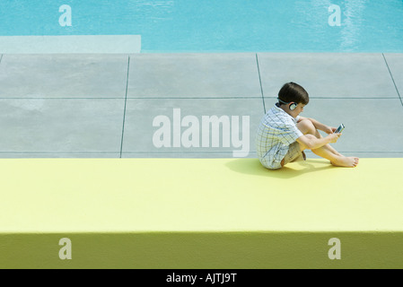 Boy sitting next to swimming pool, using handheld video device, wearing headphones - Stock Photo