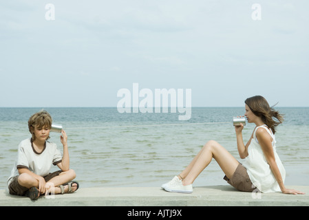 Boy and teen sister sitting next to water, talking to each other through tin can phone - Stock Photo