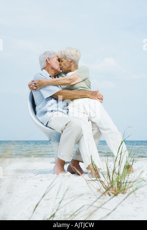 Senior couple sitting in chair together on beach, hugging and kissing, woman sitting on man's lap, full length - Stock Photo