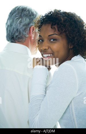 Young woman with hand on mature man's shoulder, smiling over shoulder at camera - Stock Photo