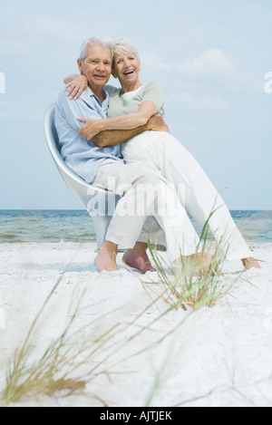 Senior couple sitting in chair together on beach, embracing, woman sitting on man's lap, both smiling at camera - Stock Photo