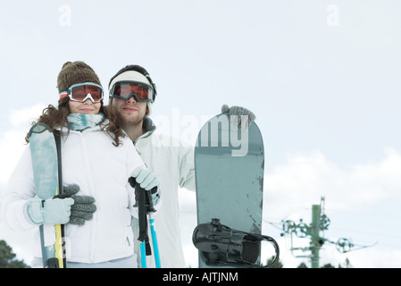 Young couple dressed in ski wear, man holding snowboard, woman holding ski sticks - Stock Photo