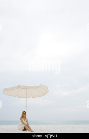 Woman wearing sundress, sitting under parasol on beach, full length - Stock Photo