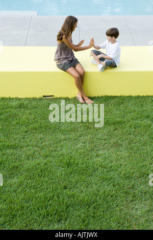 Mother and boy sitting outdoors, playing clapping game, high angle view, full length - Stock Photo