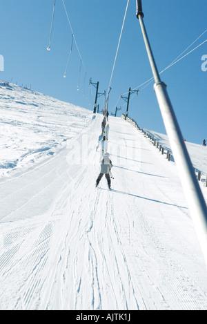 Young skiers using ski lift on ski slope, low angle view - Stock Photo