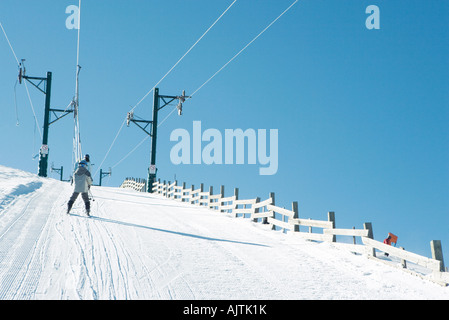 Young skier going up hill on ski lift, rear view - Stock Photo