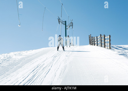 Young skiers going up hill on ski lift, rear view - Stock Photo
