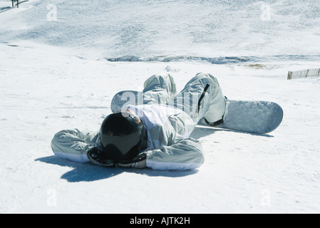 Young snowboarder lying on back in snow, hands behind head, full length - Stock Photo