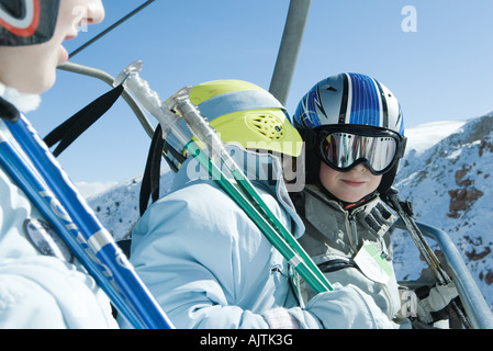 Young skiers on chair lift, one whispering in the other's ear - Stock Photo