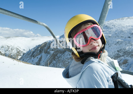 Teenage girl on ski lift, wearing goggles and helmet, looking at camera, portrait - Stock Photo