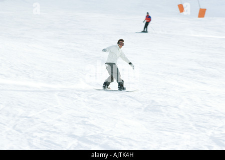 Young man snowboarding on ski slope, full length, skier in background - Stock Photo