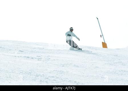 Young man snowboarding down ski slope, full length - Stock Photo