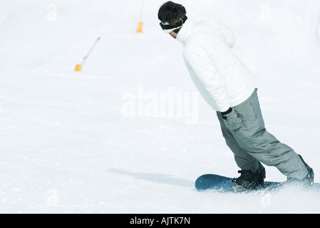 Young man snowboarding down ski slope, rear view - Stock Photo
