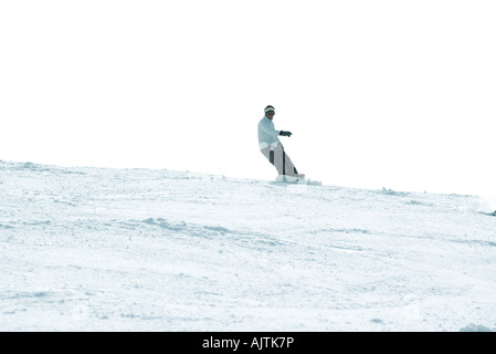 Snowboarder on ski slope, full length, in the distance - Stock Photo