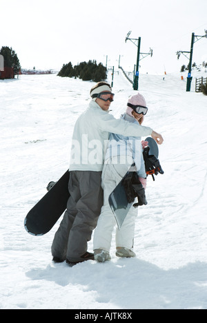 Two young snowboarders walking together, looking over shoulders at camera - Stock Photo