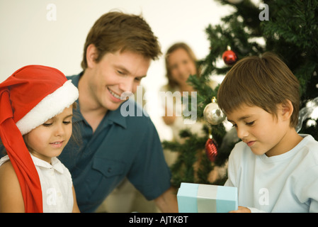 Woman And Her Daughters With Santa Hats Sitting In A