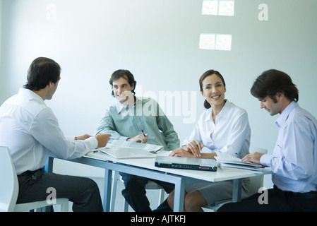 Business associates seated at table, chatting, one smiling at camera - Stock Photo