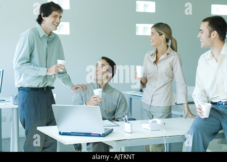 Business associates gathered around table, holding disposable cups, laughing - Stock Photo